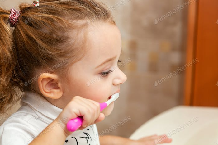 Cute little girl cleaning tooth with brush.