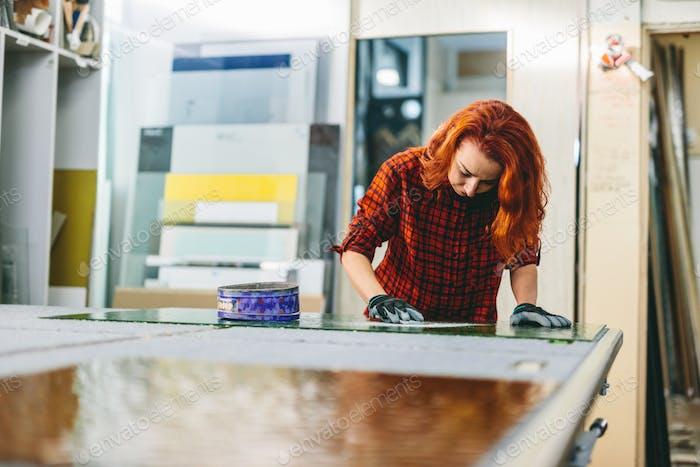Glazier woman worker polishing glass in workshop. Industry