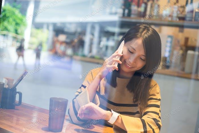 Woman talk to mobile phone and look at smart watch