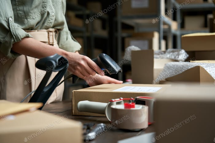 Vendedora mujer escaneando la caja de envío de comercio electrónico en el almacén dropshipping.
