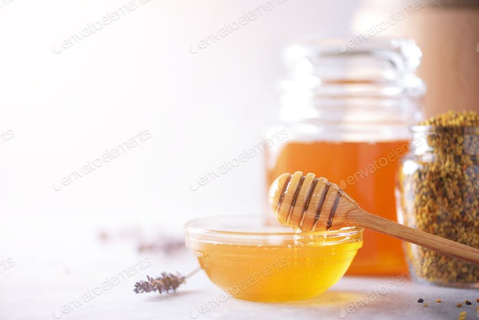 Bee pollen granules, honey jar with wooden dropper, honeycomb on grey backdrop. Copy space. Autumn