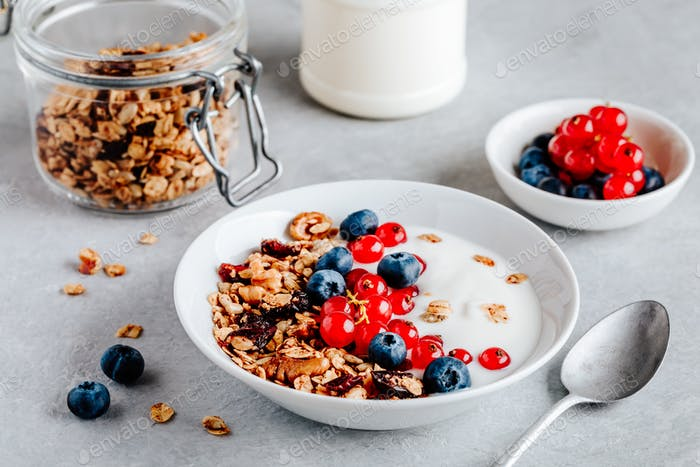 Healthy breakfast bowl with granola, blueberries, red currants and yogurt.