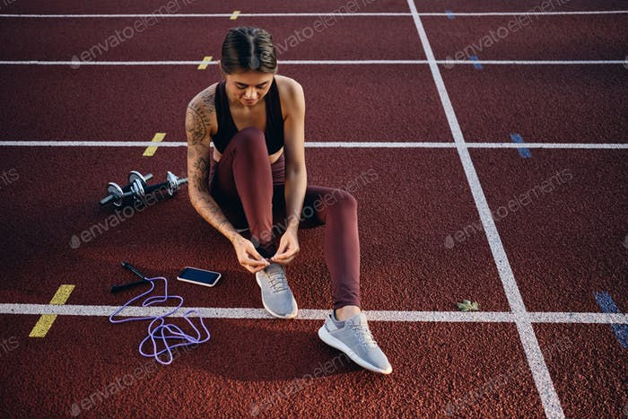 Attractive athlete girl with tattoo in sportswear tying sneaker laces before workout on stadium