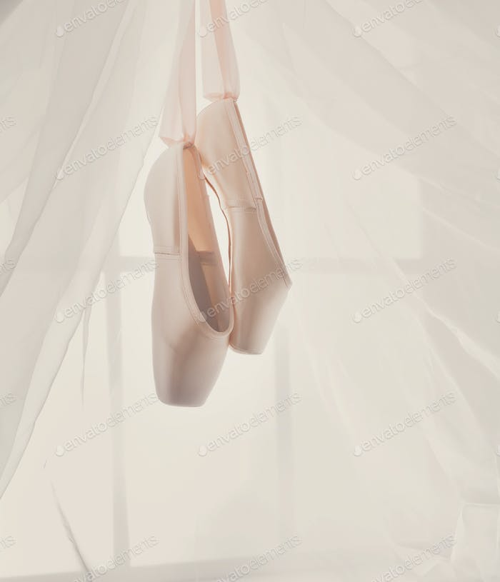 Pink ballet pointe shoes hanging on window