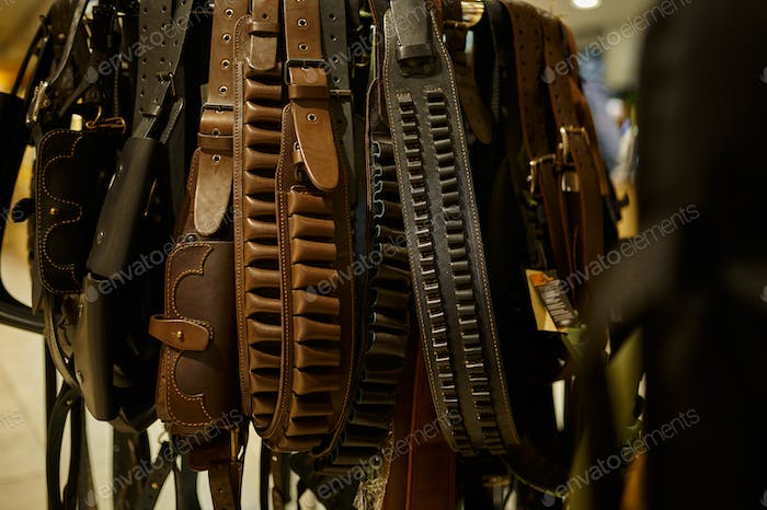 Different leather bandoliers in gun store, nobody