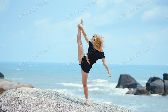 blonde girl practicing yoga by the beach