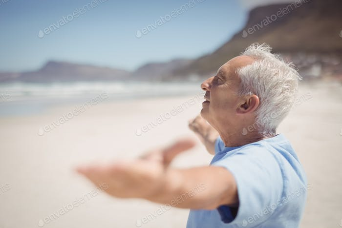Side view of senior man with arms outstretched at beach