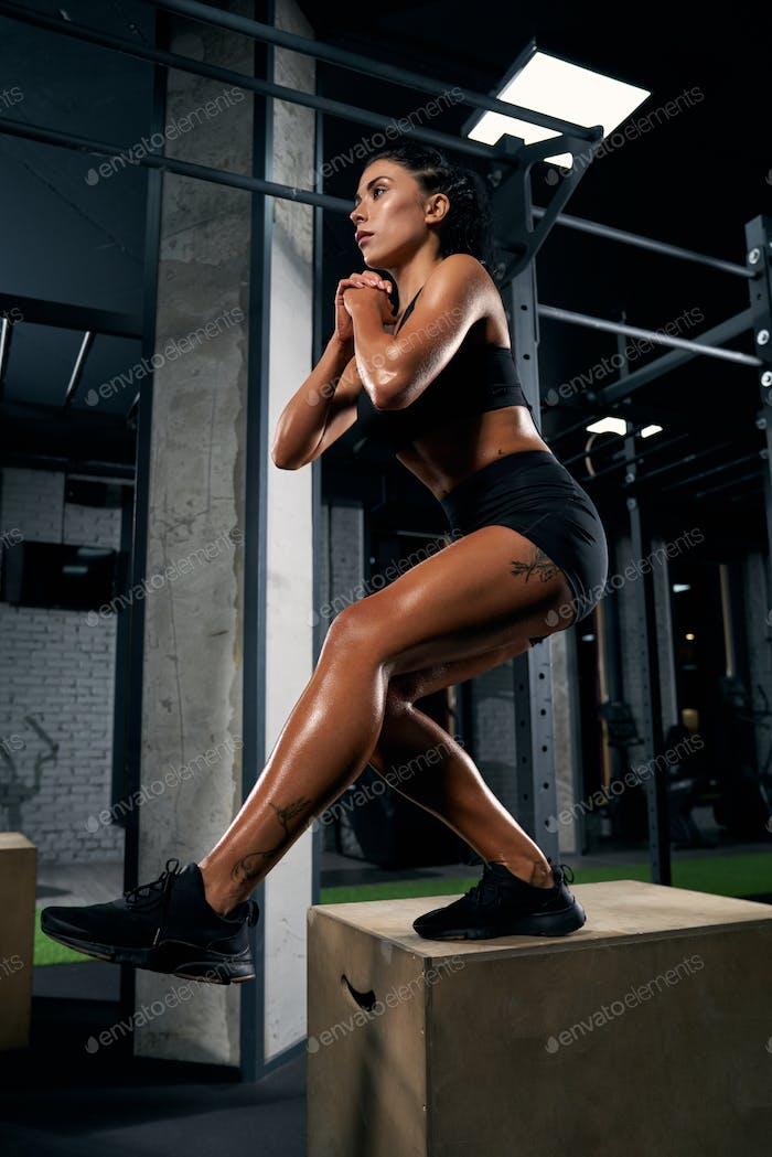 Sportlerin hockt auf Box im Fitnessstudio