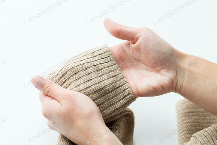close up of hands with sweater sleeve