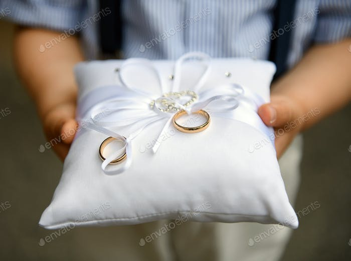 Kid holding two gold wedding bands on a cushion