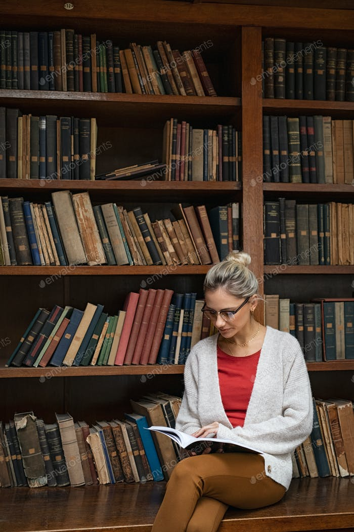 Young woman in library reading book