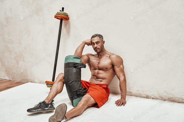 Healthy and handsome athlete sitting on the floor wearing red shorts and holding sport gear