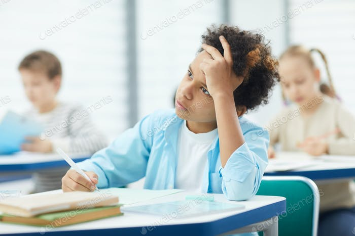 Pensive Mixed-Race Boy In Classroom