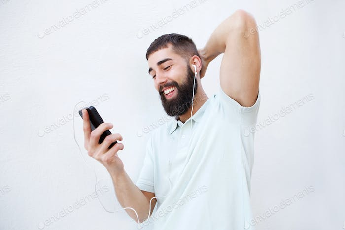 Cheerful man with headphones and cellphone with hand to head