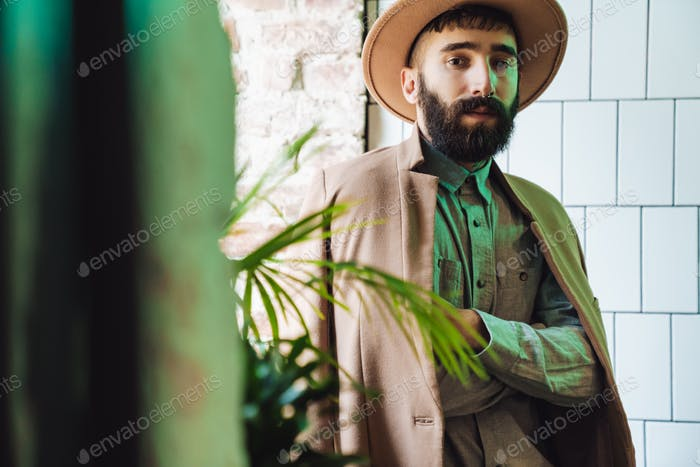 Attractive young bearded man wearing coat