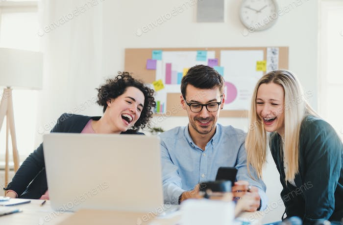 Group of young businesspeople with laptop working together in a modern office.