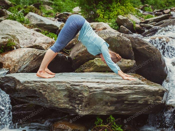 Junge sportlich fit Frau tun Yoga im Freien an tropischen Wasserfall