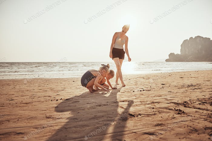 Smiling Mother watching her kids playing on a sandy beach