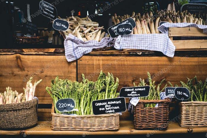 Frischer grüner und weißer Spargel auf dem Markt