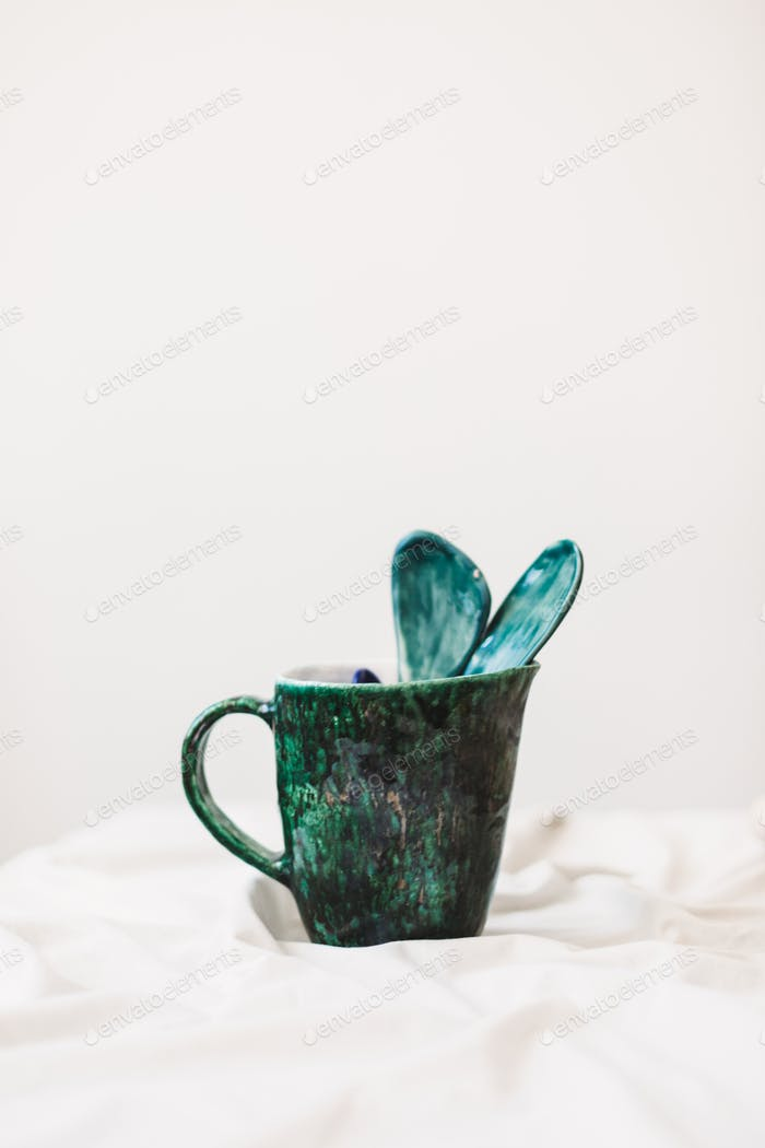 Close up photo of handmade colorful mug and spoons at pottery studio isolated