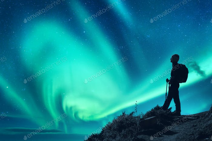 Aurora borealis and silhouette of a woman with backpack at night