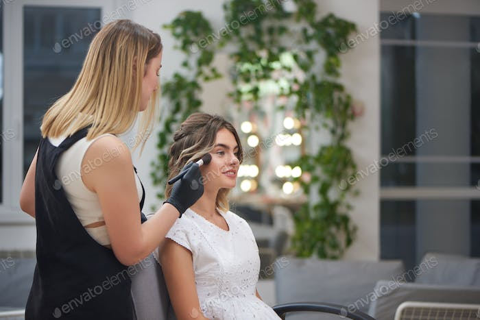 Charming client getting professional makeup in beauty salon