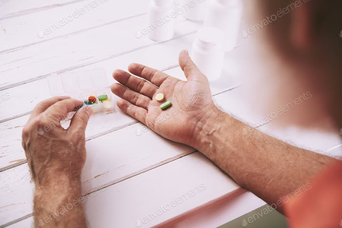 Aged man taking painkillers