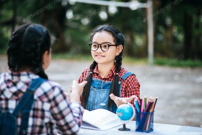 Две обучающие девушки разговаривают друг с другом в парке