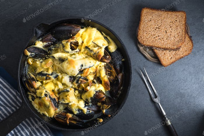 Mussels with cheese sauce in a frying pan, bread on a saucer, fork
