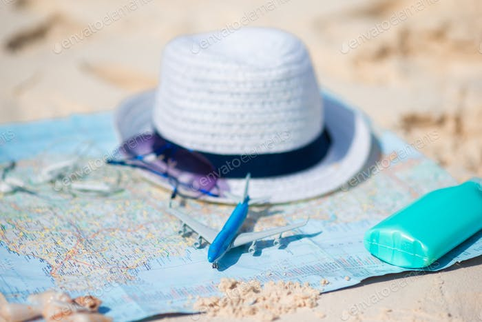 Traveling concept. Hat, suncream, sunglasses on a map of the world