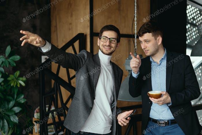 Geschäftsmänner Gespräch, zeigend Hand zum Fenster