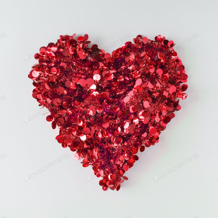 Heart shape made of red glitter on bright background. Flat lay. Love concept.