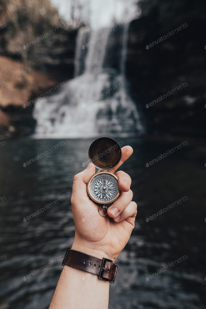 Holding compass in front of waterfall