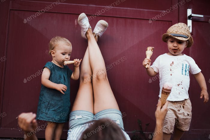 A young mother with two toddler children outdoors in summer, eating ice cream.