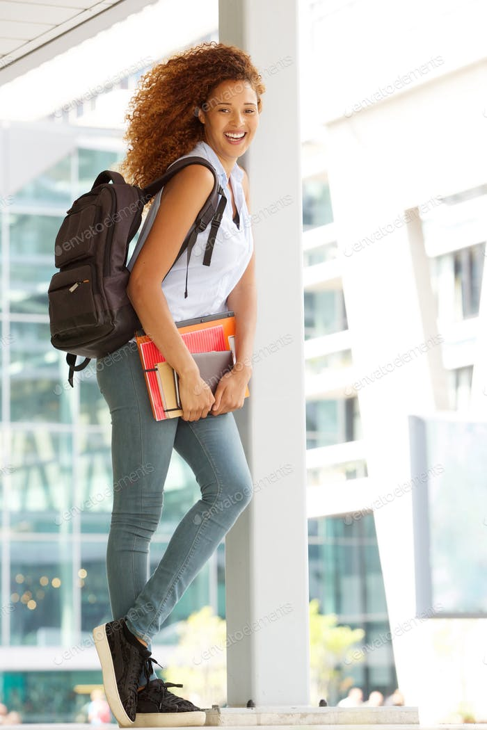 Full body happy female student standing outside with bag and books