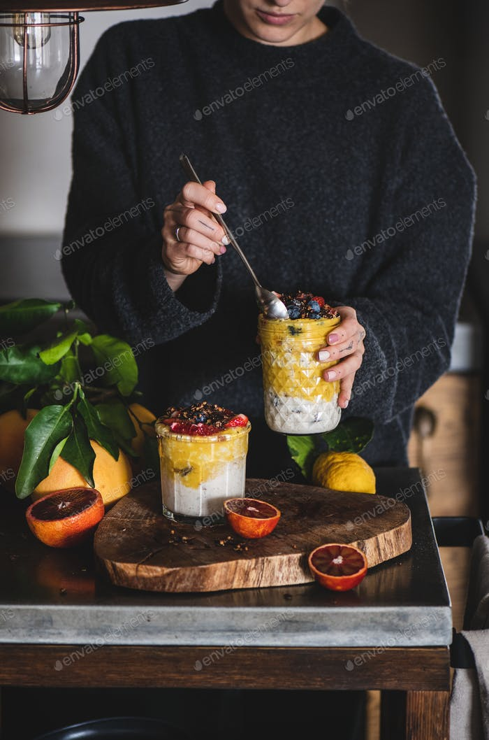 Woman eating muesli with mango smoothie and granola from glass
