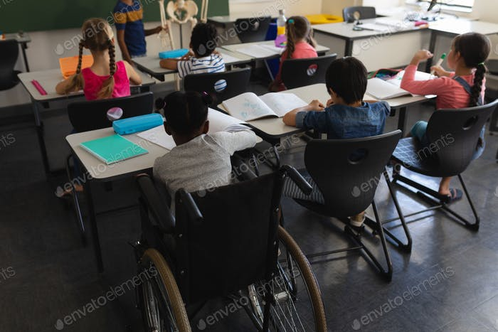Disable schoolboy studying at desk in classroom