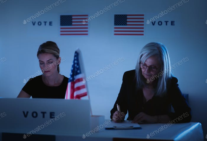 Tired members of electoral commission in polling place at night time, usa elections