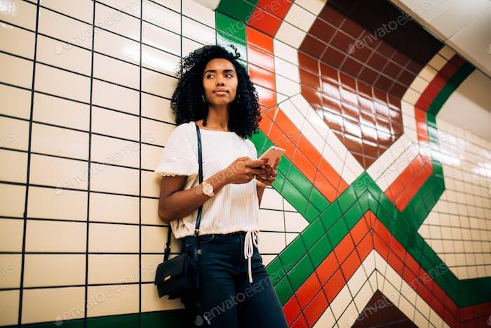 Mujer usando el teléfono móvil mientras está de pie en la estación de metro