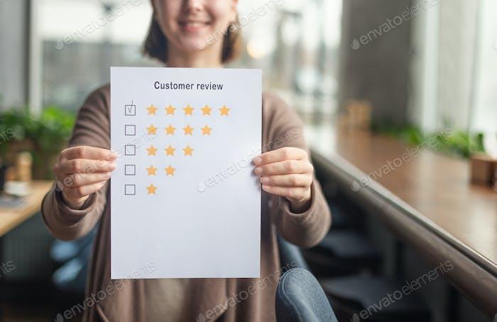 Unerkennbare Frau zeigt fünf Sterne Bewertung Coworking Ort