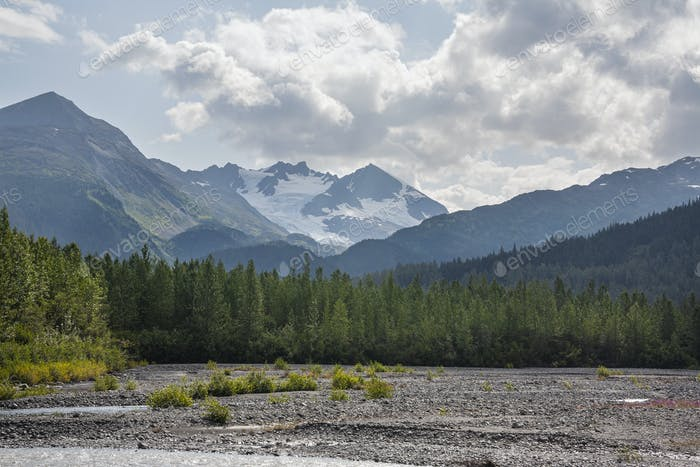 Mountains in Alaska above a glacial streambed on a sunny afternoon