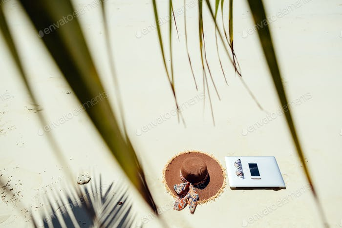 laptop and smartphone on beach remote work