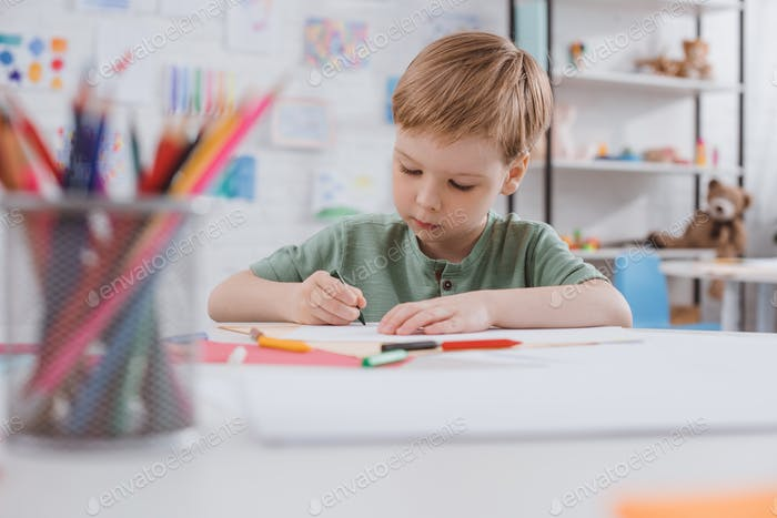 portrait of preschooler drawing picture with pencils at table in classroom