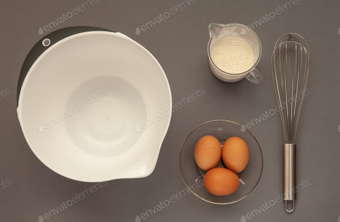 Whisk and a plastic cup for whipping on a gray background