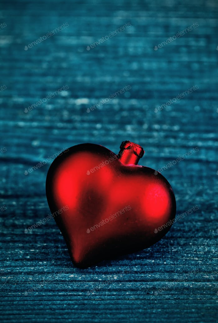 Red heart on the blue wooden background