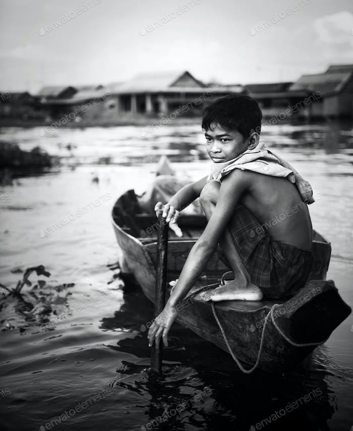 Junge Reisen mit dem Boot im schwimmenden Dorf