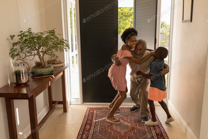 Front view of a happy African American grandfather embracing his grandchildren at home