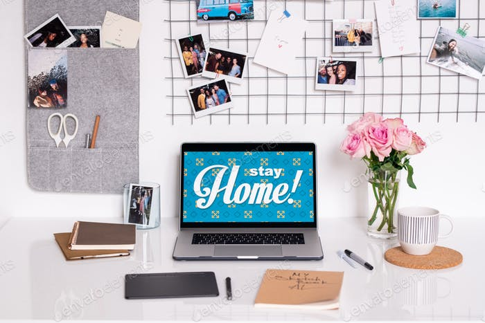 Wall with photographs and desk with supplies of contemporary designer