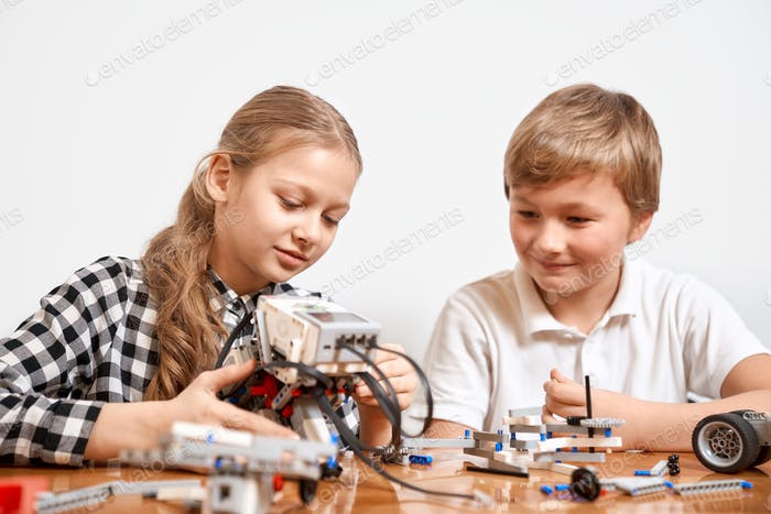 Young friends creating robot using building kit