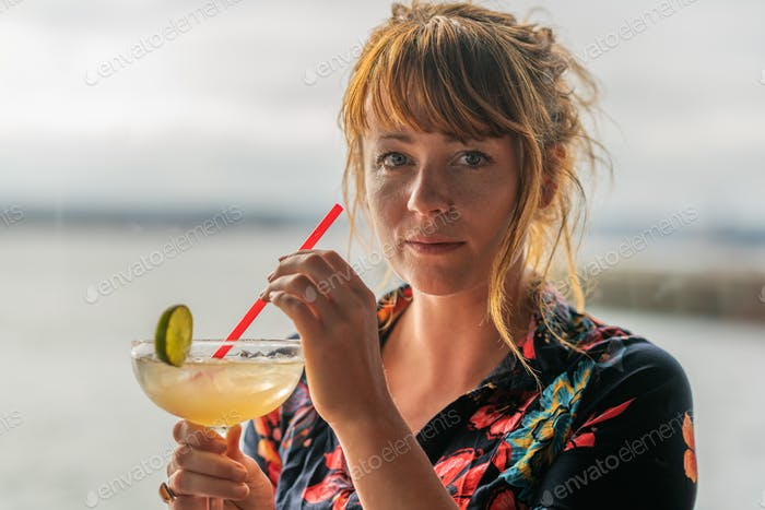 Ginger girl with blue eyes and floral dress drinking a mojito